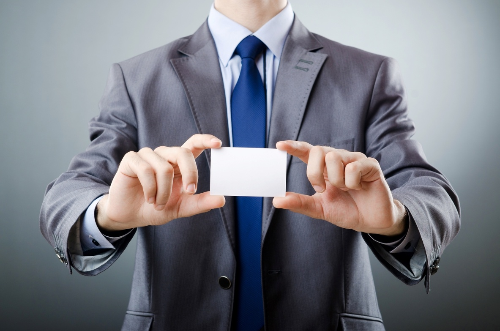 Businessman_holding_blank_business_card.jpg