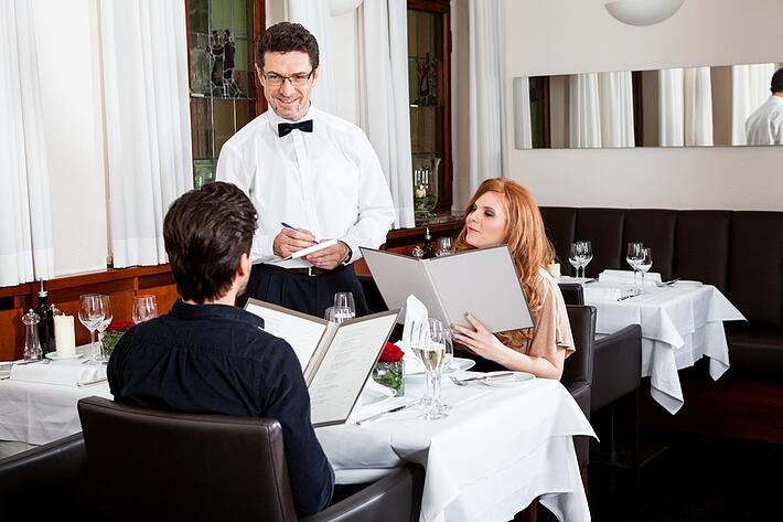 Couple looking at menus in upscale restaurant with waiter