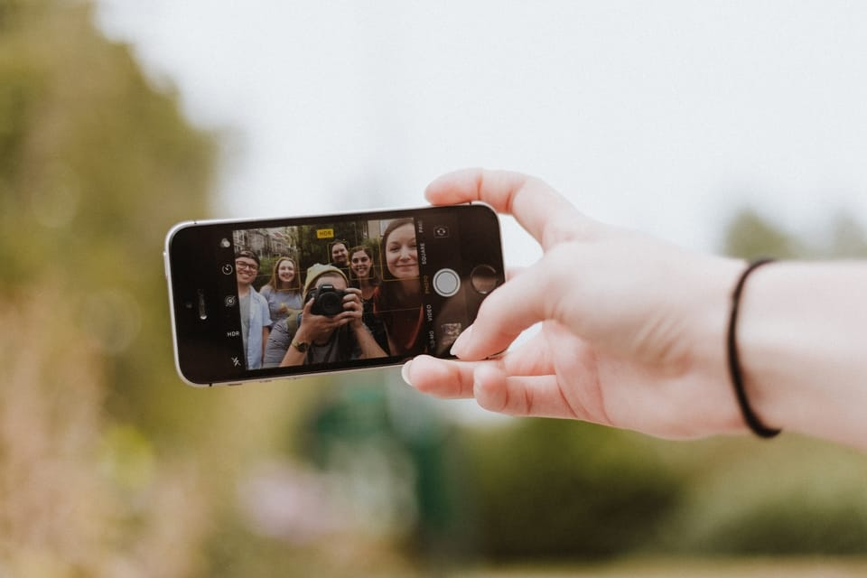 group of six people taking a photo on an iphone