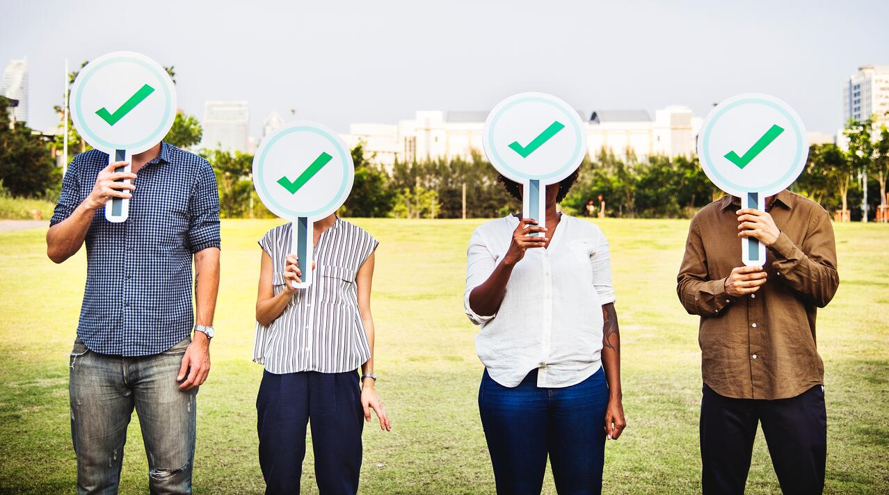 four-people-holding-checkmark-signs